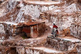 Quechua woman, worker's hut and salt evaporation terraces at Las Salineras, Maras, near Cusco, Peru