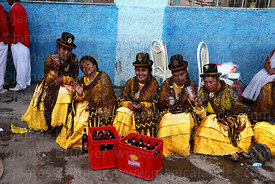 Dance group drinking at street party after formal parades, Virgen de la Candelaria festival, Puno, Peru