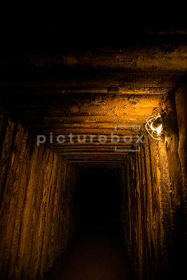 An atmospheric image of a darkly lit underground tunnel / bunker.
