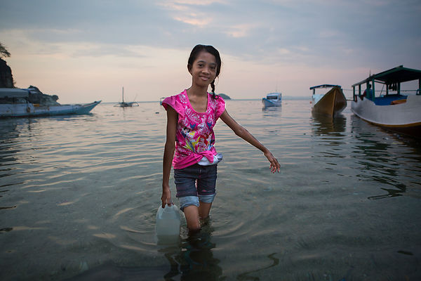Nabila, 11 ans, va chercher de l'eau de mer dans les bidons, eau qui sera utilisée pour tirer la chasse des toilettes Pulau Messah, Flores, Indonésie / Nabila, 11 years old, fetches sea water in the cans, water that will be used to flush toilets Pulau Messah, Flores, Indonesia