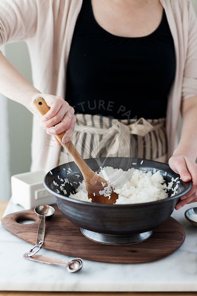 The making of sushi. Woman mixing rice in a bowl.