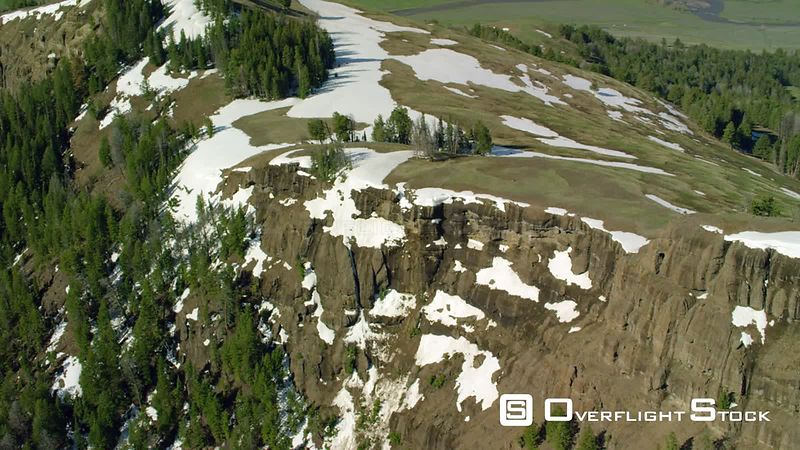 Snowcapped peaks and steep cliffs overlook the Lamar Valley within the southern flank of the Absaroka mountain  Range in Yellowstone National Park