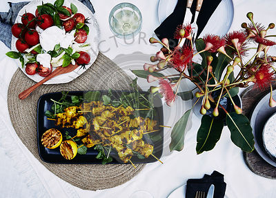 Table setting of mediterranean salad and grilled turmeric chicken skewers.