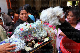 A woman has her skulls blessed with holy water as she leaves church after mass, Ñatitas festival, La Paz, Bolivia