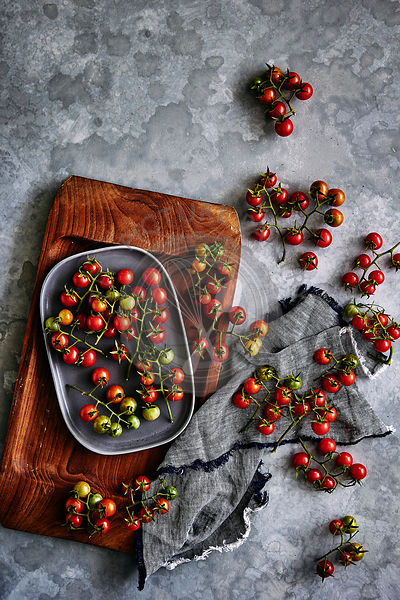 freshly picked red cherry tomatos from the garden, displayed on a wooden and grey board.