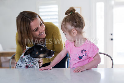 Woman and Little Girl in Kitchen with Dog