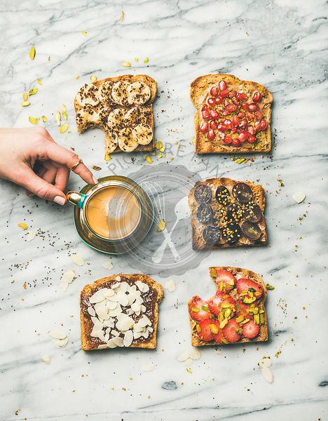 Healthy breakfast with wholegrain toasts and woman's hand taking coffee