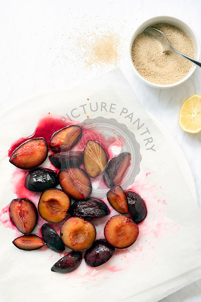 Roasted red plums in syrup on baking paper with a bowl of brown sugar and half a squeezed lemon.