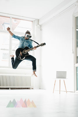 Man with guitar wearing Virtual Reality Glasses jumping in the air in a loft