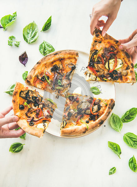 People's hands taking Freshly baked vegetarian pizza over marble background