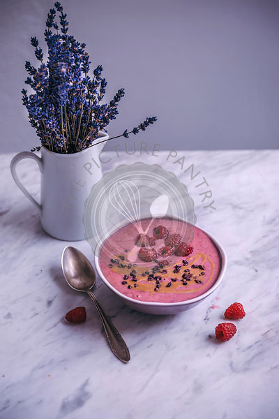Raspberry smoothie bowl topped with peanut butter, raspberries and cacao nibs