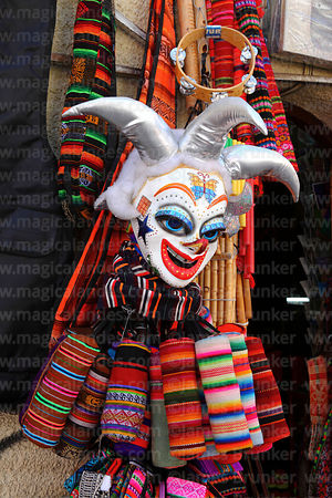 Pepino carnival mask and textiles outside shop in tourist market area, La Paz, Bolivia