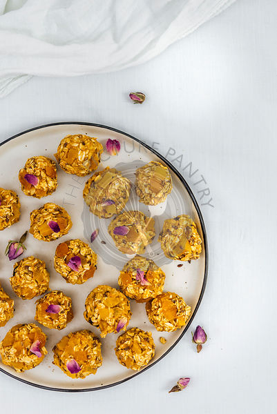 No-Bake Pumpkin Energy Balls with apricots, oats and flax seeds on a plate photographed on a white background from top view.