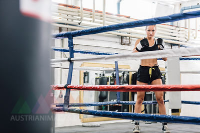Portrait of confident female boxer in boxing ring