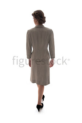 A 1940's / 1950's woman in a suit, walking away – shot from eye-level.
