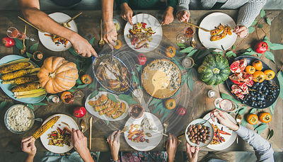 Friends feasting at Thanksgiving Day table with turkey and wine