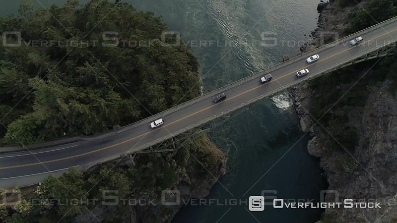 Flying over travelers in commute on high bridge with tall cliffs from Pacific Ocean islands. Deception Pass Washington USA