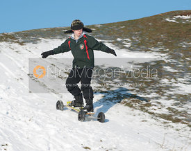 Young boy on off road skateboard skates to camera on snow