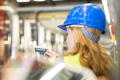 Woman wearing reflective vest controlling industrial plant with digital tablet