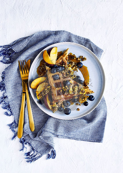 Healthy and light glutin free blueberry waffles with buckweat and nut turmeric muesli, golden peaches, fresh blueberrys and maple syrup .