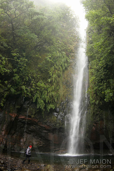 Hiker under a waterfall in sub-tropical forest