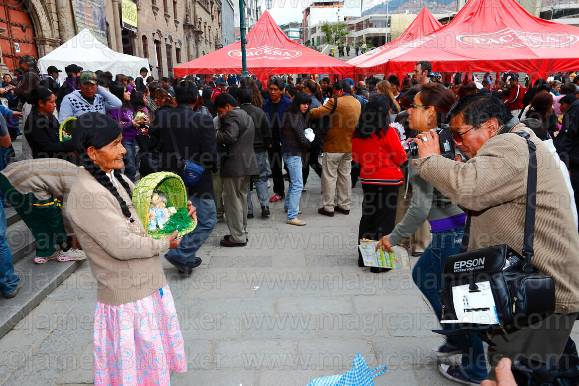 Photographer taking photo of woman holding her baby Jesus figure outside church after mass for Reyes (Epiphany, January 6th), La Paz, Bolivia