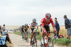 Group of Cyclists Riding on a Cobblestone Road - Tour de France 2015