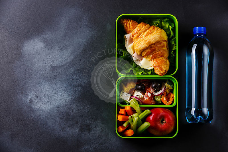 Take out food Lunch box with Croissant sandwich, Greek salad and vegetables with bottle of water on blackboard background copy space