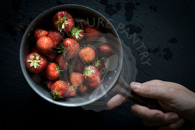 Hand holding vintage colander with strawberries on black slate. Top view