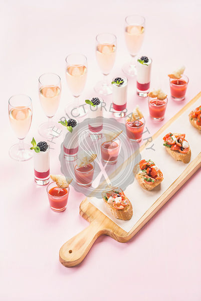 Various snacks, brushetta sandwiches, gazpacho shots, desserts with berries in glasses on corporate event, christmas, birthday party or wedding celebration over pastel pink background