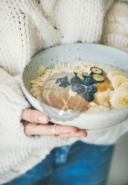 Woman in jeans and sweater holding bowl of oatmeal porriage