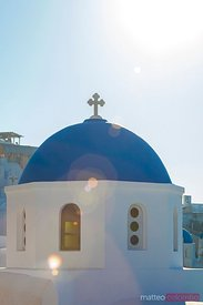 Sunlight over blue domed church in Santorini, Greece