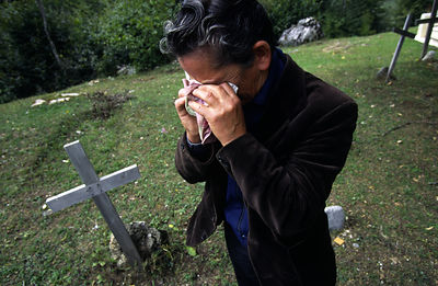 Albania - Thethi - Pashke Sokol Ndocaj cries at the grave of her father