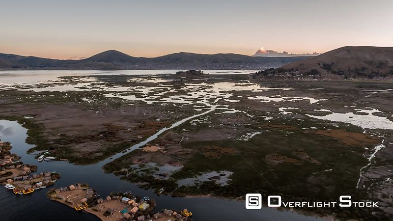 Aerial view of Floating Island Uros ( Isla de los Uros ), Lake Titicaca, filmed by drone at sunset, Peru
