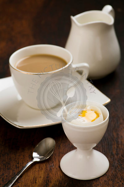 coffee with milk and boiled egg in eggcup