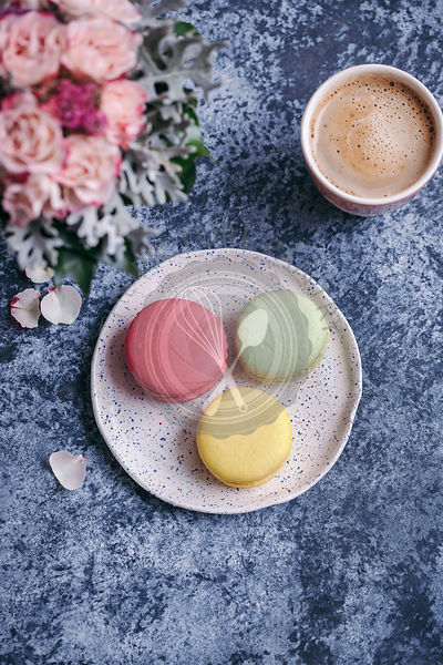 Macarons on a dessert plate and a cup of coffee on grey background