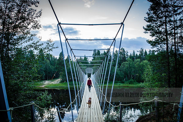 Photographer walking on a bridge during the night in summer in Lapland
