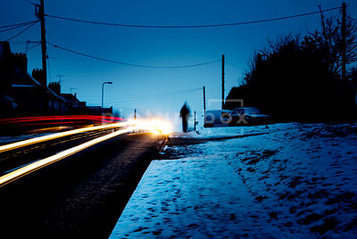 An atmospheric image of a snow covered street a dawn with a shadowy figure being passed by a speeding car.