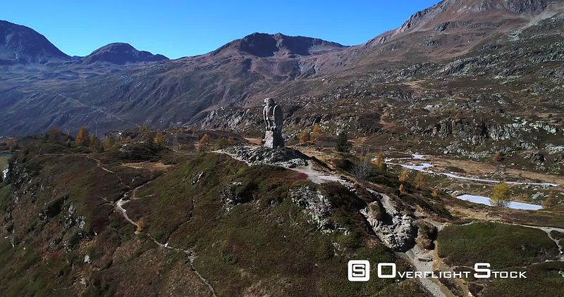 Stone Statue, 4k Aerial Vertigo Effect View of the Eagle Statue Monument, on the Top of Simplon Pass, Sunny Autumn Evening, Valais, Switzerland