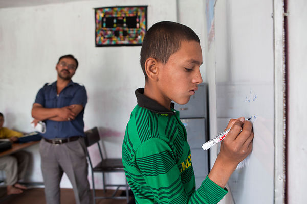 Bashir 13 ans écrit au tableau en classe, Kaboul, Afghanistan / Bashir 13 years-old is writting at the board in class, Kabul, Afghanistan