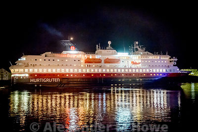The Fully Lit Hurtigruten ship NORDNORGE steaming out of Svolvær harbour at night