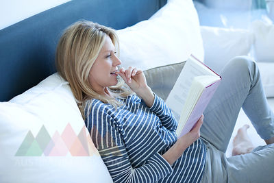 Woman reading book on a couch