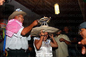 Man lighting fireworks on a womans hat with cigarette before she runs into crowd, San Ignacio de Moxos, Bolivia