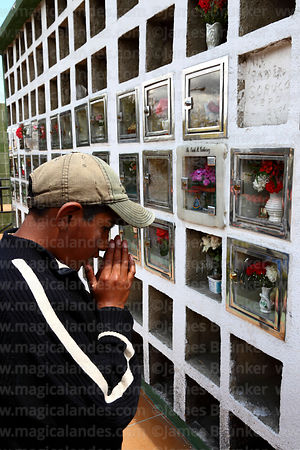 Boy saying prayers for souls of the dead in cemetery during Todos Santos festival, La Paz, Bolivia
