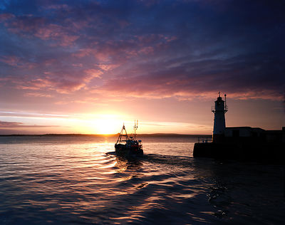 Spectacular sunrise over Mount's Bay with the trawler off to work once more passing the lighthouse at the end of Newlyn harbour wall.