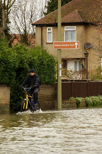 Man Cycles Through Flood Waters Past Sign for Hinksey Outdoor Pool