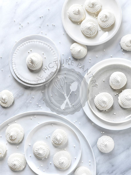White meringue cookies on white plates on a light marble surface with pearl sprinkles scattered around the frame.