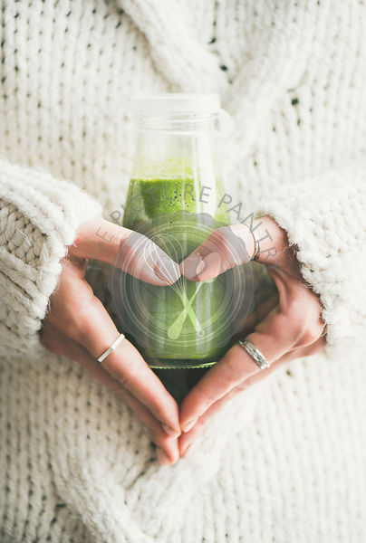 Healthy smoothie or juice in bottle in woman's hands