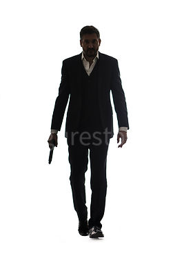 A mystery man in a suit, walking with a gun, in silhouette – shot from low level.