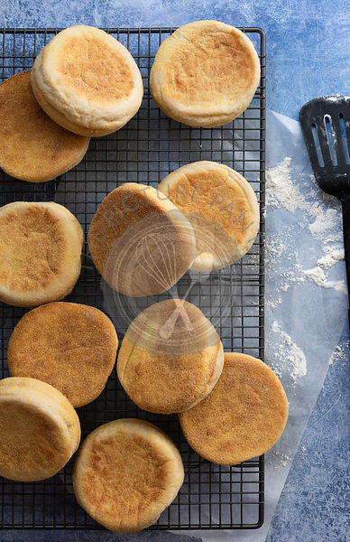 English muffins cooling on a wire rack from a top view.
